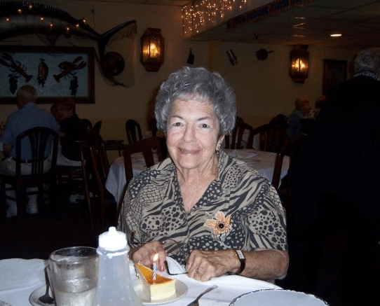 woman sitting at a dinner table with a birthday candle