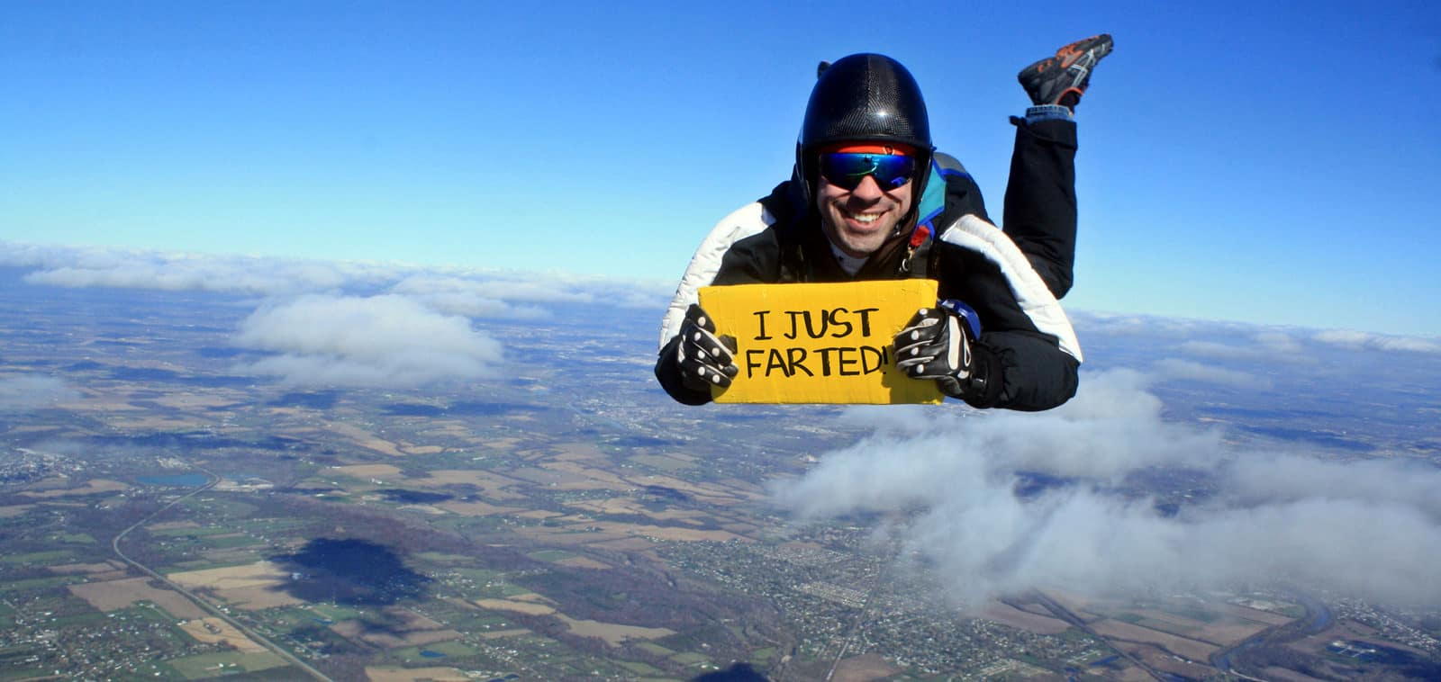 man skydiving holding a sign