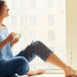 woman relaxing and drinking coffee in front of a large window
