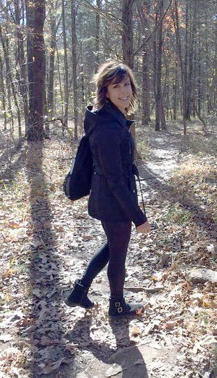 Denise walking down a wooded trail smiling