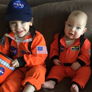 two boys on couch in astronaut outfits