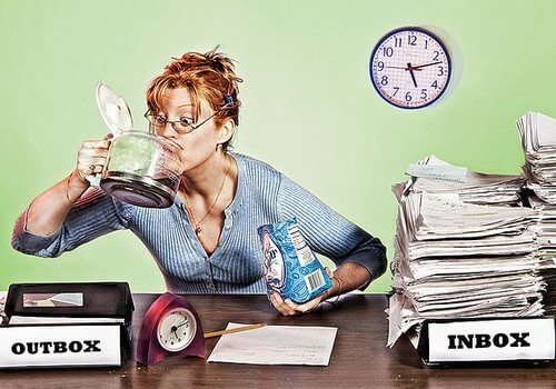 Woman drinking coffee with work piled up.